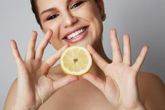 Beauty women with big blue eyes and dark eyebrows holding fresh limon and smiling at camera over gray background.Model Stock Photos