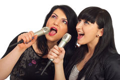 Beauty women singing at karaoke. Happy beauty two women singing in microphones at karaoke party and looking up to screen isolated on white background Royalty Free Stock Image