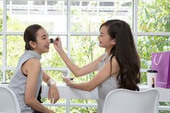 Two friends making up in the cafe. Young beautiful woman with Makeup Brush. stock photography