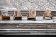 Beauty in Wood - Assorted comfy wooden chairs sit on a wooden deck at waterside stock photo