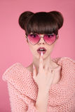 Beauty wow. Fashion surprise teen girl model. Brunette in heart. Sunglasses with matte lips and hairstyle posing over studio pink background royalty free stock images