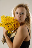 Beauty with yellow flowers. There is women with yellow flowers looks on the side stock photos