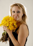 Beauty with yellow flowers. There is women with yellow flowers looks on the side stock photography
