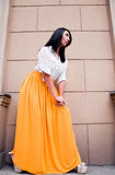 Beauty in yellow skirt. Photography from below of pretty brunette fashion female model wearing white shirt and long maxi bright yellow skirt and posing near Royalty Free Stock Image