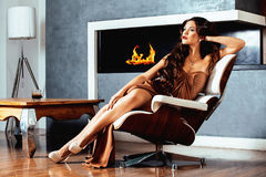 Beauty yong brunette woman sitting near fireplace at home Stock Image