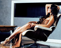 Beauty yong brunette woman sitting near fireplace at home, lifes Stock Images