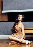 Beauty yong brunette woman sitting near fireplace at home, winte Stock Image