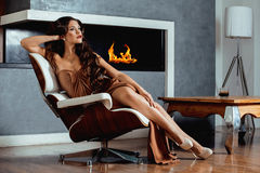 Beauty yong brunette woman sitting near fireplace Stock Images