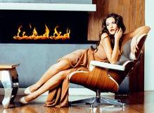Beauty yong brunette woman sitting near fireplace at home Stock Photo
