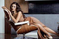 Beauty yong brunette woman sitting near fireplace Stock Image