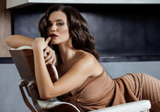 Beauty yong brunette woman sitting near fireplace Stock Photo