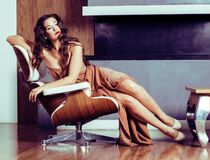 beauty yong brunette woman sitting near fireplace at home, winte royalty free stock images