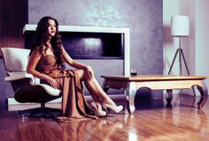 Beauty yong brunette woman sitting near fireplace at home, winte stock images