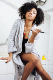Beauty young african american woman in bathrobe with tooth brush taking morning care of herself, lifestyle concept Royalty Free Stock Photography