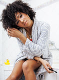 Beauty young african american woman in bathrobe with tooth brush taking morning care of herself, lifestyle concept. Beauty young african american woman in Stock Image