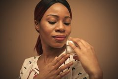 Beauty. Young African woman with face cream. stock photography