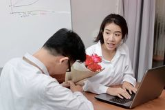 Beauty young Asian woman getting a bouquet of red roses in office on valentine`s day. Love and romance in workplace concept. Royalty Free Stock Photography