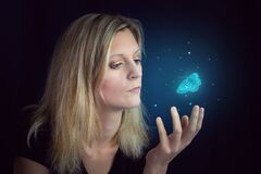 Beauty young blond hair woman hold hand under glowing blue butterfly. Photomanipulation glowing lepidopteran on black background
