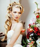 Beauty young blond woman bride alone in luxury vintage interior with a lot of flowers Royalty Free Stock Images