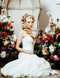 Beauty young blond woman bride alone in luxury vintage interior with a lot of flowers. Close up Stock Photo