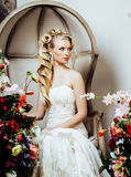 Beauty young blond woman bride alone in luxury vintage interior with a lot of flowers. Close up Stock Photos