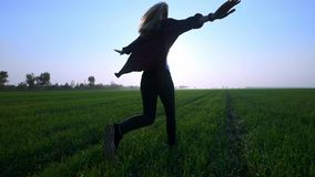 Beauty young blondie girl running on green wheat field over sunset sky. Freedom concept. Happy woman outdoors. Harvest