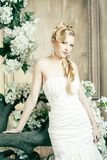 Beauty young bride alone in luxury vintage interior with a lot of flowers, makeup and creative hairstyle. Closeup royalty free stock image
