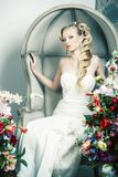 Beauty young bride alone in luxury vintage interior with a lot of flowers, makeup and creative hairstyle. Closeup stock images