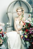 Beauty young bride alone in luxury vintage interior with a lot of flowers, makeup and creative hairstyle. Closeup royalty free stock images