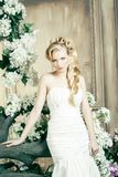 Beauty young bride alone in luxury vintage interior with a lot of flowers, makeup and creative hairstyle. Closeup stock photography