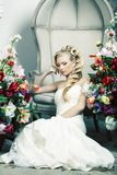 Beauty young bride alone in luxury vintage interior with a lot of flowers, makeup and creative hairstyle. Closeup stock photo