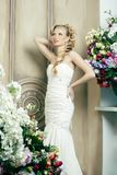 Beauty young bride alone in luxury vintage interior with a lot of flowers, makeup and creative hairstyle. Closeup stock image