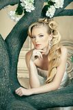 Beauty young bride alone in luxury vintage interior with a lot of flowers, makeup and creative hairstyle. Closeup royalty free stock photos