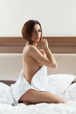 Beauty young brunette wear towel and relax in bed Stock Images