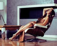 Beauty young brunette woman sitting near fireplace at home, luxury interior, people on holiday royalty free stock photos