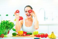 Beauty young funny woman holding fresh vegetables in her kitchen at home Stock Photo