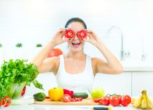 Beauty young funny woman holding fresh vegetables in her kitchen at home Royalty Free Stock Images