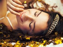 Beauty young girl in gold confetti and tiara Royalty Free Stock Photography