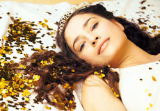 Beauty young girl in gold confetti and tiara. Little princess celebration close up smiling Royalty Free Stock Image