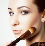 Beauty young Girl with Makeup Brushes. Natural Make-up for Brunette Woman with bleu Eyes. Beautiful Face. Makeover. Perfect Skin. Stock Photos