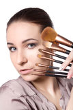 Beauty young Girl with Makeup Brushes. Natural Make-up for Brunette Woman with bleu Eyes. Beautiful Face. Makeover. Perfect Skin. On the white background Royalty Free Stock Photos