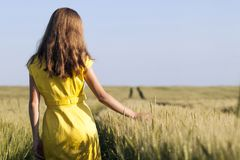 Beauty young girl outdoors enjoying nature. Beautiful teenage mo. Del girl in yellow dress walking on the wheat field in sun light stock photos