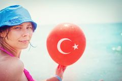 Beauty young girl on sea beach with balloon of Turkish flag in hand, Turkey. Tropical resort vacation on beach Royalty Free Stock Photography