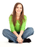 Beauty young girl sitting on the floor with crossed legs, smilin Stock Image