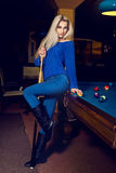 Beauty young lady plays billiard on pool table Royalty Free Stock Photos