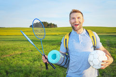 Beauty young man enjoys fun traveling with a backpack  rackets and ball, smiling on  background of green meadows Royalty Free Stock Photos