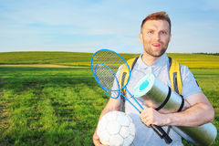 Beauty young man on picnic with backpack and rackets for a badbotton, ball smiling against a green meadow Royalty Free Stock Photos