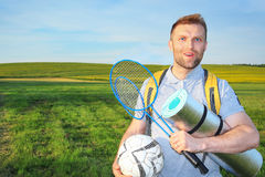 Beauty young man on picnic with backpack and rackets for a badbotton, ball smiling against a green meadow Royalty Free Stock Image