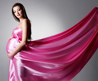 Beauty of young pregnant woman. In beautiful pink dress- grey background Royalty Free Stock Photo