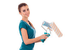 Beauty young slim builder girl makes renovations with paint roller isolated on white background Stock Image